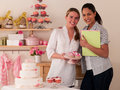 Decorating cakes two happy young women Royalty Free Stock Photography
