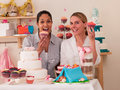 Decorating cakes two happy young women Stock Image