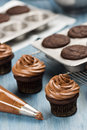 Decorating chocolate cupcakes with frosting from a pastry bag on a blue table Stock Images