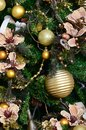 Decorating Christmas tree close up. Decoration bulb, green fir tree, golden x-mas toys and lights. Use for Christmas and New years Royalty Free Stock Photo