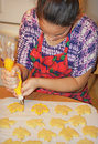 Decorating cookies a woman baker leaf for fall with yellow frosting Royalty Free Stock Image