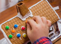 Decorating a gingerbread house with chocolate drops Royalty Free Stock Images