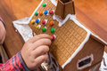 Decorating a gingerbread house with chocolate drops Royalty Free Stock Image