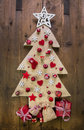 Decoration handmade carved christmas tree with red miniatures and white Stock Photography