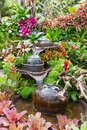 Decoration jar with the fountain in the garden. Decorative jar with fountain  look like waterfall with flowers and tree plant in Royalty Free Stock Photo