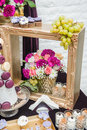 Decoration with pink, white and red flowers in golden wooden frame. Wedding decor with grapes and cookies. Fresh roses Royalty Free Stock Photo