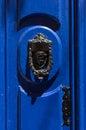 Decorative bronze door handle on a blue painted door. Malta Royalty Free Stock Photo