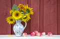 Decorative ceramic jug pitcher with sunflowers and apples beautiful fresh ripe summer end still life Stock Images