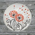 Decorative ceramic plate, hand painted with acrylic paints on a wooden background. A square photo closeup
