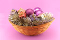 Decorative christmas basket on pink background conceptual image about with colorful gift boxes purple gold and silver ornaments Royalty Free Stock Images