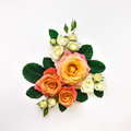 Decorative composition of orange and white roses, green leaves on white background. Flat lay, top view
