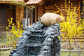 Decorative garden waterfall with stone jar Royalty Free Stock Photo