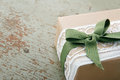 Decorative gift box wrapped in brown eco paper white lace and green bow on wooden vintage background with copy space Royalty Free Stock Images