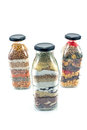 Decorative glass bottles with seeds isolated on white Royalty Free Stock Images
