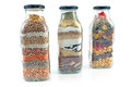 Decorative glass bottles with seeds on white Royalty Free Stock Photo