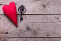 Decorative  heart and vintage key on aged wooden background. Royalty Free Stock Photo
