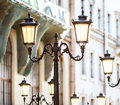 Decorative lamp posts the fragment of old city central street with beautiful lights and details of classic facades on the Royalty Free Stock Photo