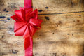 Decorative red bow on rustic wood background ribbon and a with copyspace to celebrate a merry christmas romantic valentines day or Stock Photos