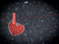 Decorative red heart hanging against dark light bokeh background concept of valentine day with space for text Stock Photography