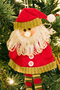 Decorative santa claus on christmas tree closeup of fabric hung up with lights Stock Photo