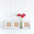 Decorative shelf on white brick wall with flowers in vase on it Royalty Free Stock Images