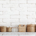 Decorative shelf on white brick wall with vintage bottles and wicker jars on it Royalty Free Stock Images