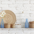 Decorative shelf on white brick wall with vintage bottles and wicker jars on it Royalty Free Stock Photography