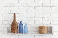 Decorative shelf on white brick wall with vintage bottles and wicker jars on it Royalty Free Stock Image