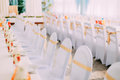 Decorative White Mantles And Colored Ribbons On Chairs At Festive Table.