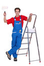 Decorator holding paint roller by a step ladder Stock Photos