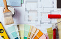Decorator s work table with tools painter and house project color swatches painting roller and paint brushes top view Royalty Free Stock Photography