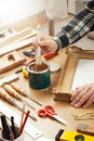 Decorator varnishing a wooden frame hands close up with diy tools hobby and craft concept Stock Images