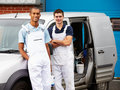 Decorators wearing overalls standing next to van looking camera smiling Royalty Free Stock Photo