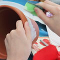 Decoupage on flower pot hands of a child masters getting started Royalty Free Stock Images