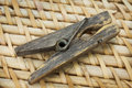 Decrepit wooden clothespin on a straw mat lying Royalty Free Stock Photos