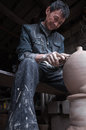 A dedicated chinese potter was making traditional pot for wine in his workshop Royalty Free Stock Images