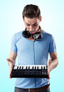 Deejay with headphones holding midi keyboard in hands while being surprised gradient blue background Stock Photos