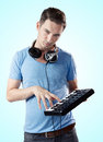 Deejay with headphones pressing keys on midi keyboard portrait of young serious controller gradient blue background Stock Photo