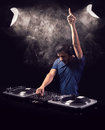 Deejay mixing at party being excited while playing music from vinyl with one raised hand he is illuminated by two vintage spot Stock Photo