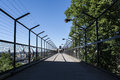 Deep perspective of a walkway with high fences Royalty Free Stock Photo