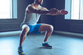 Deep squat part of young man in sportswear doing at gym Stock Photo