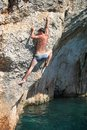 Deep water soloing male rock climber on cliff rear view Royalty Free Stock Image