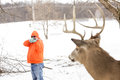Deer hunter taking aim at a whitetail deer in orange focus on Royalty Free Stock Photo
