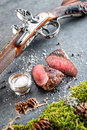 Deer or venison steak with antique long gun and ingredients like sea salt and pepper, food background for restaurant or hunting lo Royalty Free Stock Photo