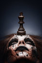 Defeated by chess king a creative photo of a queen with a painted pierced face and a in her mouth Royalty Free Stock Image
