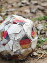 Defect not usable abandoned football in a garden old weathered standard size white black with graphics of national flag on ground Stock Images