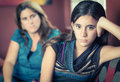 Defiant teenage girl and her worried mother teenager problems after a fight with looking at Royalty Free Stock Photo