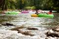 Defocused People Tubing Down River Approach Boulders In Focus Royalty Free Stock Photo