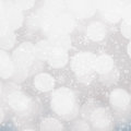 Defocused silver and white christmas bokeh background with snowf snowflakes festive blur high resolution Royalty Free Stock Images