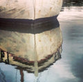 Defocused white boat reflecting in water Royalty Free Stock Photo